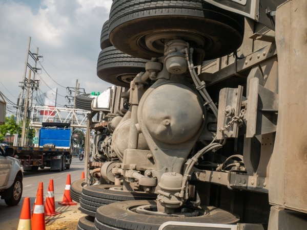 A view of under the truck carrying a container overturned on a road under a bridge over an t20 e94xdL